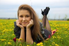 A smiling girl laying on the grass with yellow flowers. Girl laying on the grass with yellow dandelions facing camera and smiling Stock Photo