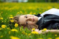 A smiling girl laying on the grass with yellow flowers. Girl laying on her back on the grass with dandelions facing camera and smiling Royalty Free Stock Photo
