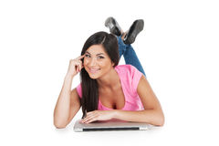 Smiling girl laying  with laptop having legs crossed. Royalty Free Stock Photo