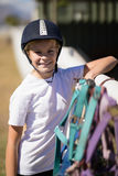 Smiling girl leaning on the fence next to horse reins and muzzle Royalty Free Stock Photo