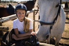 Smiling girl leaning on the fence in ranch. Portrait of smiling girl leaning on the fence in ranch royalty free stock image