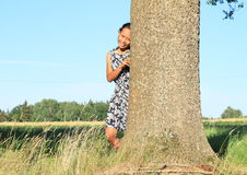 Smiling girl leaning on tree Stock Images