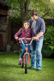 Smiling girl learning how to ride a bicycle with her father at p Stock Photography