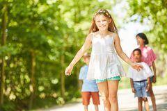 Smiling girl is learning to skateboard. Smiling girl learns to skateboard in summer with friends Royalty Free Stock Photo