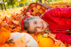 Smiling girl on leaves with pumpkin and apples Stock Image