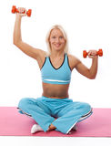 Smiling girl lifting dumbbells Stock Photo