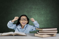 Smiling girl lifting hands with books in classroom Royalty Free Stock Image