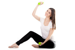 Smiling girl lifts green color dumbbells Stock Images