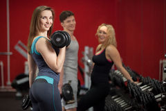 Smiling girl lifts weights in fitness center, with friends on th Stock Images