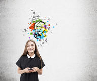 Smiling girl and light bulb sketch, concrete wall Stock Photography