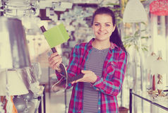 Smiling girl in lighter shop is choosing stylish and modern lamp Royalty Free Stock Image