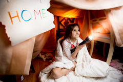 Smiling girl lighting bedroom at night with flashlight Stock Photography