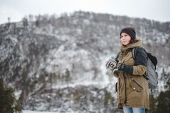 Smiling girl listening the music in winter mountains. Smiling young woman with backpack listening the music in winter mountains by white headphones stock photo