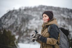 Smiling girl listening the music in winter mountains. Smiling young woman with backpack listening the music in winter mountains by white headphones royalty free stock images