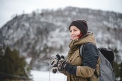 Smiling girl listening the music in winter mountains. Smiling young woman with backpack listening the music in winter mountains by white headphones royalty free stock photos