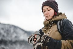 Smiling girl listening the music in winter mountains. Smiling young woman listening the music in winter mountains by white headphones. Mobile phone in her hands stock photo