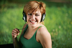 Smiling girl listening to music with headphones. Smiling pretty girl listening to music with headphoness sitting on the grass stock image