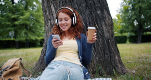 Smiling girl listening to music in headphones using smartphone relaxing in park. Smiling girl is listening to music in headphones and using smartphone relaxing stock video