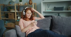 Smiling girl listening to music through headphones using smartphone at home. Smiling girl is listening to music through headphones and using smartphone relaxing stock video