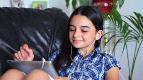 Smiling girl listening to music on tablet pc stock video