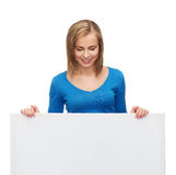 Smiling girl lkooking at blank white board Stock Photo