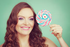 Smiling girl with lollipop candy on teal Stock Photography