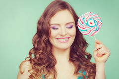 Smiling girl with lollipop candy on teal Stock Photos