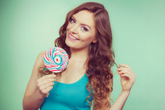 Smiling girl with lollipop candy on teal Royalty Free Stock Photos