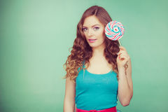 Smiling girl with lollipop candy on teal Royalty Free Stock Image