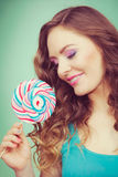 Smiling girl with lollipop candy on teal Royalty Free Stock Photography