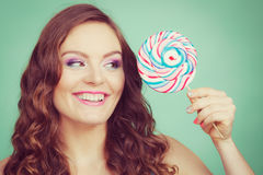 Smiling girl with lollipop candy on teal Stock Photo