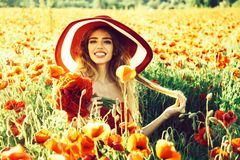 Smiling girl in field of poppy seed in retro hat royalty free stock photo