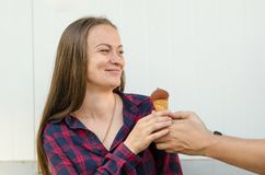 Smiling girl with long hair and freckles takes ice cream from hands of man stock images