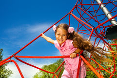 Smiling girl with long hair stands on red rope Stock Image