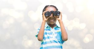 Smiling girl looking through binoculars over blur background Royalty Free Stock Photos