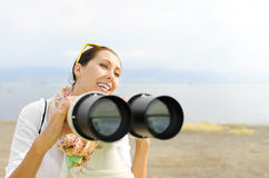 Smiling girl looking through binoculars Stock Photos