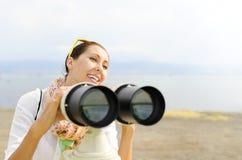 Smiling girl looking through binoculars Stock Photos