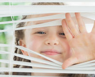 Smiling girl looking through the blinds Royalty Free Stock Photos