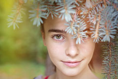 Smiling girl looking through blurred fir needles Stock Photos