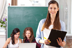Smiling  girl looking at camera in college Royalty Free Stock Photos
