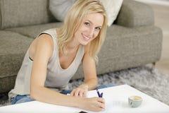Smiling girl looking at camera while making notes