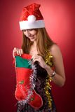 Smiling girl looking into Christmas stocking stock image