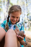 Smiling girl looking at dry pine cone through magnifying glass in the forest Royalty Free Stock Photos