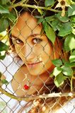 Smiling girl  looking through the grid Royalty Free Stock Photos