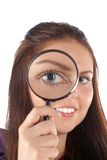 Smiling girl looking through magnifying glass Royalty Free Stock Photo