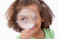 Smiling girl looking through a magnifying glass Stock Photos