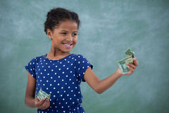 Smiling girl looking at paper currency Stock Photo