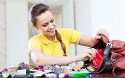 Smiling girl looking for something in handbag. At table in home Royalty Free Stock Image