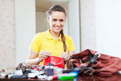 Smiling girl looking for something in purse. In home Royalty Free Stock Photography