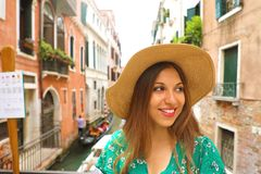 Smiling girl looking to the side in Venice. Portrait of happy young tourist woman with hat on Venice canal, Italy royalty free stock images